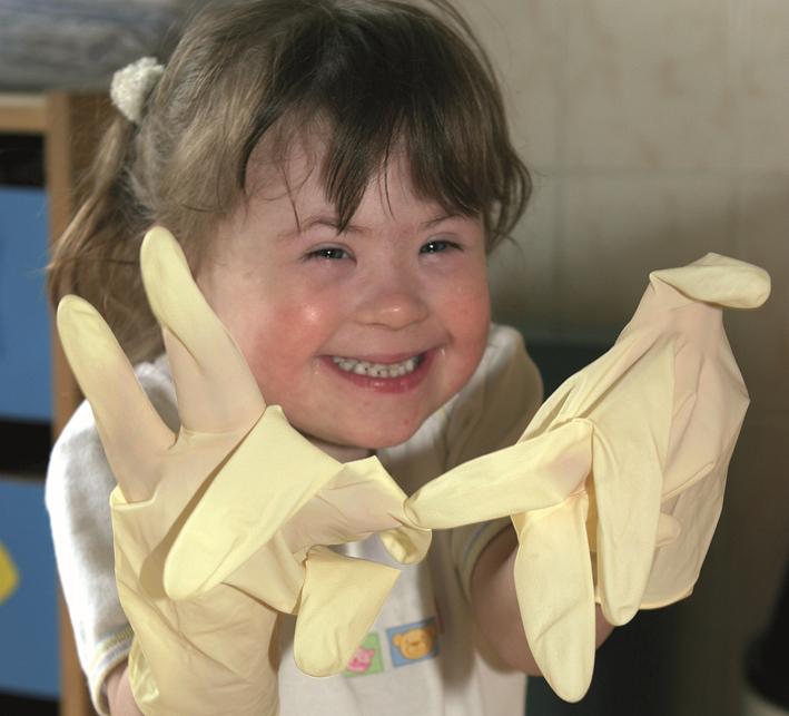 Behindertes Kind mit Putzhandschuhen